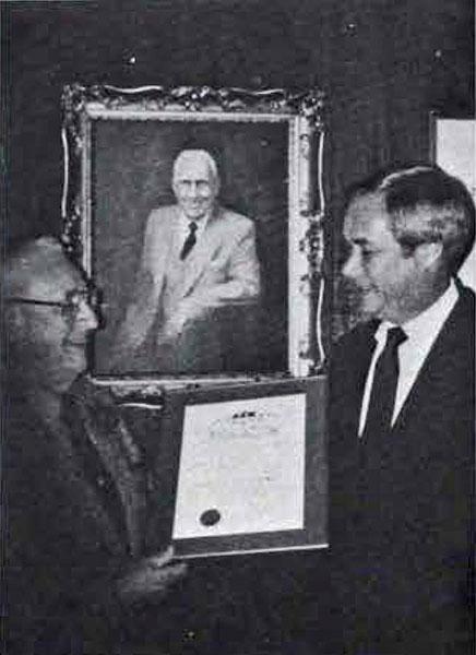 Delta Sigma Pi - Delta Tau Chapter, George J. Eberhart shows Dean Edward L. Goebel his Golden Helmet Award, 1983