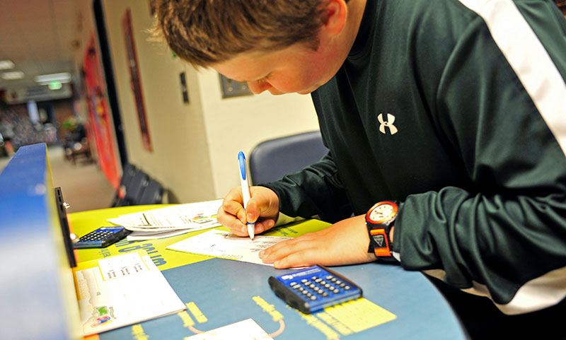 Luke Metzger, 11, fills out his check to pay for his entry onto the Money Bus at DeVaney Elementary School.
