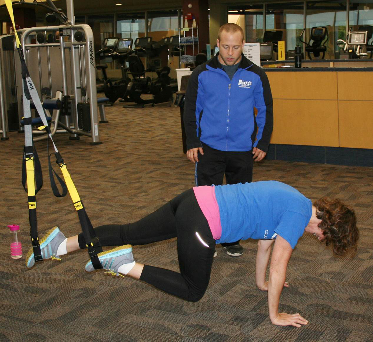 Keri works the TRX strap with Brandon's guidance
