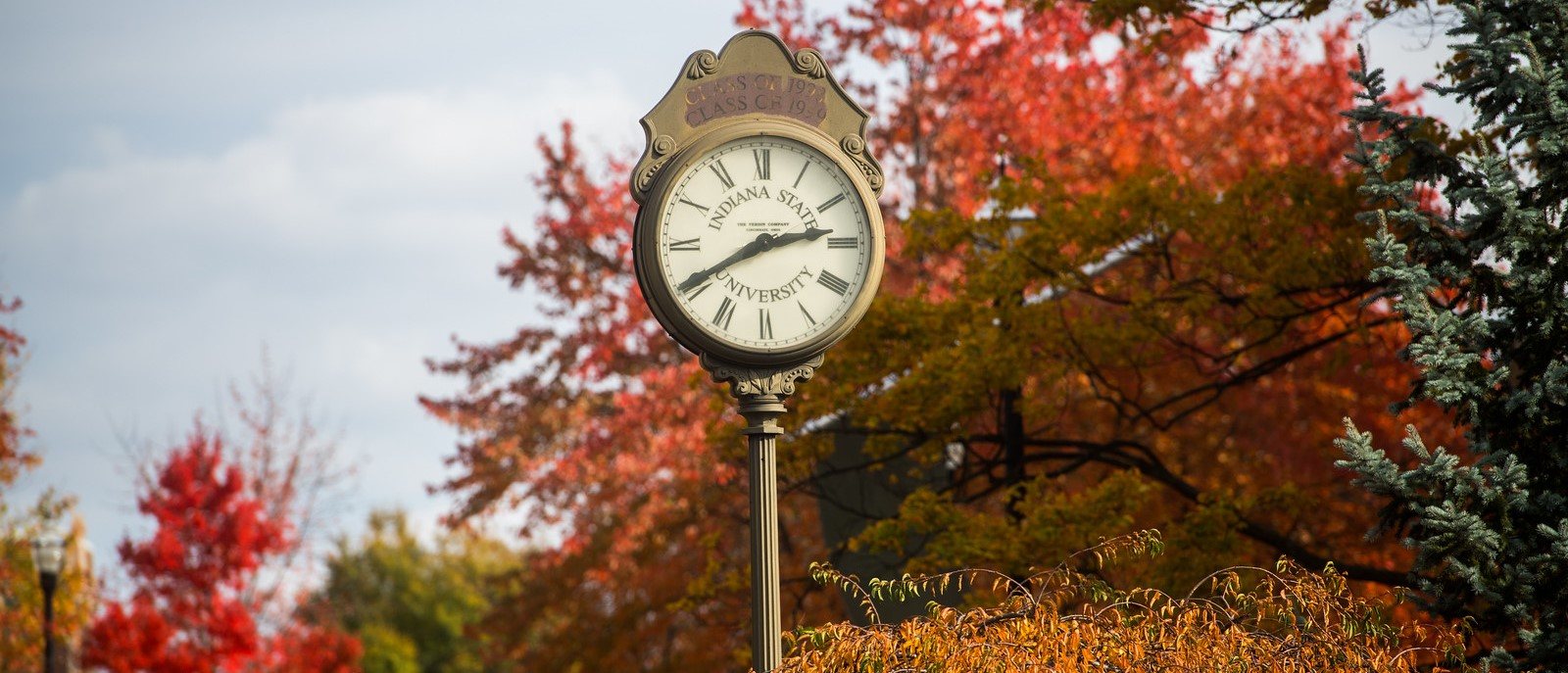 Campus clock surrounded by fall trees