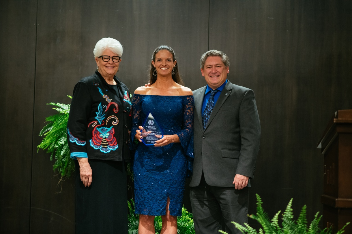Picture of Dr. Carrie Ball with Provost Licari and President Curtis accepting the graduate Provost's Award