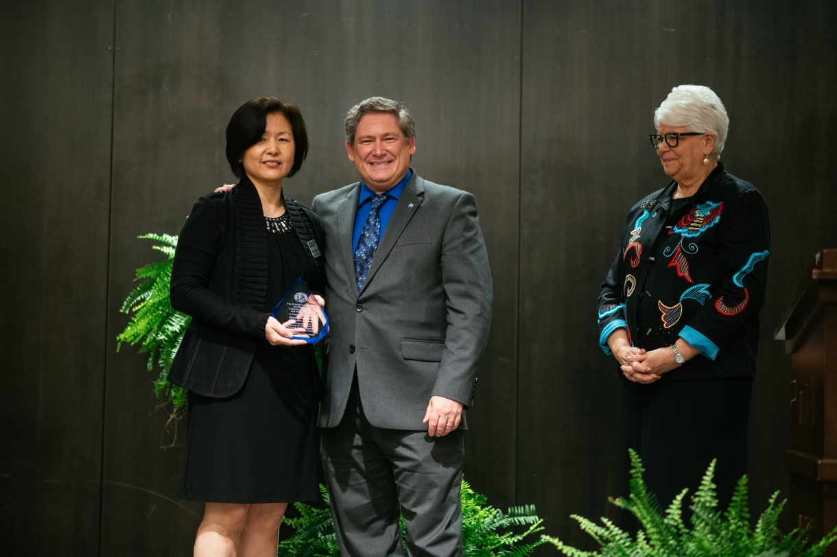 Picture of Dr. Myung-ah Lee with Provost Licari and President Curtis accepting the undergraduate Provost's Award