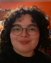a young woman with glasses and curly hair