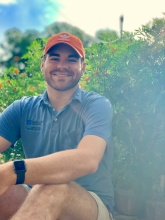 garrett in the garden with a blue polo and orange hat